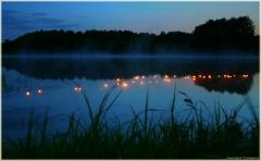 Ночное озеро. Плавающие свечи. Туман над поверхностью воды