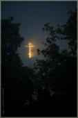 Церковный крест в лучах рассвета сквозь туман