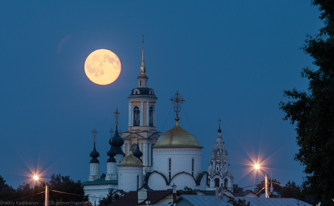 Фотография огромной луны на фоне колокольни